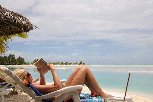 Läser bok på stranden